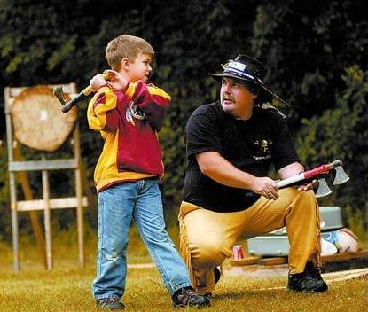 Camp Chair teaching a scout to throw Tomahawks